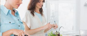 Photo of two women preparing a salad in the kitchen